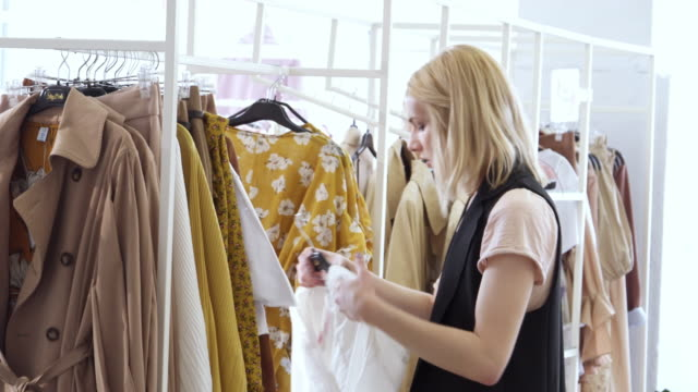 Transgender person choosing outfit in boutique