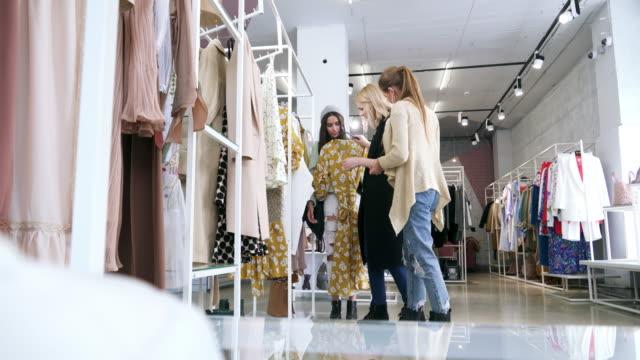 Transgender person helping female friend choosing dress in fashion boutique