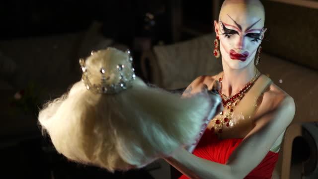 stockvideo's en b-roll-footage met transgender zetten pruik op - pruik