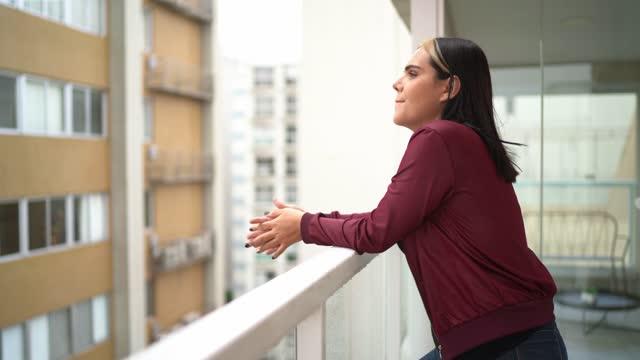transgender-frau auf dem balkon der wohnung mit blick auf die aussicht - nur junge frauen stock-videos und b-roll-filmmaterial