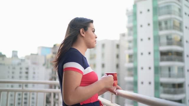 vídeos de stock, filmes e b-roll de mulher transgênero olhando para a vista na varanda do apartamento - olhar para o outro lado