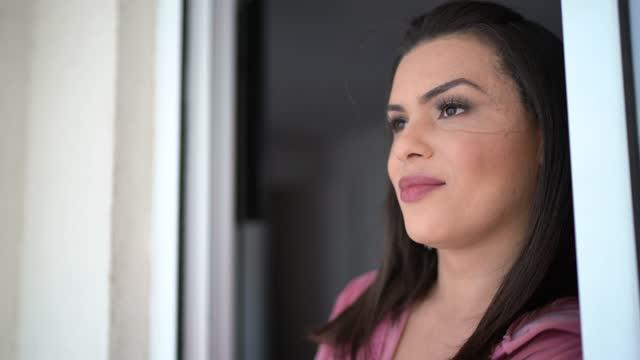 vídeos de stock, filmes e b-roll de mulher transgênero olhando pela janela em sua casa - nostalgia