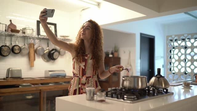 vídeos de stock, filmes e b-roll de mulher transgênero usando smartphone para fazer uma chamada de vídeo ou vlogging enquanto cozinha em casa - film moving image