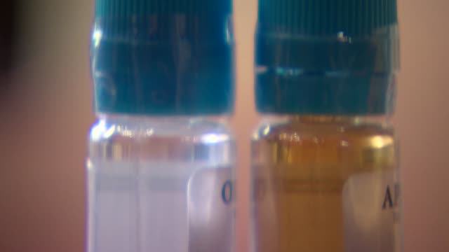 transparent bottles with fluid - nikotin stock-videos und b-roll-filmmaterial