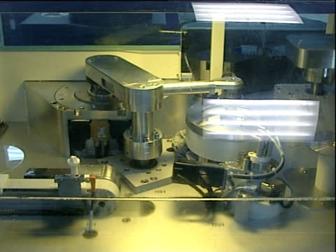 transparent compact discs are transferred from one machine to another during manufacturing process - cd stock-videos und b-roll-filmmaterial