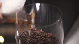 A transparent container with coffee beans and more beans are falling into it form the packet before grinding. Coffee making in a bar. Low angle view.