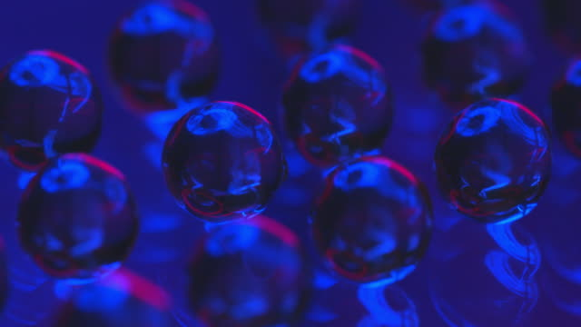 transparent glass balls on glossy surface. beautiful light passes through them, which is refracted and reflected. - aluminium stock videos & royalty-free footage