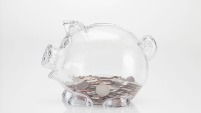 vídeos de stock, filmes e b-roll de transparent piggy bank filling up with coins on white background - enchendo