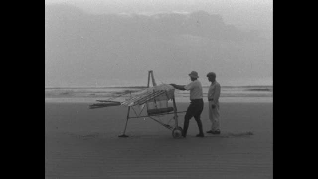 transparent winged contraption with rising sun behind / vs inventor george white testing the wings / white seated in apparatus being towed behind... - 発明家点の映像素材/bロール