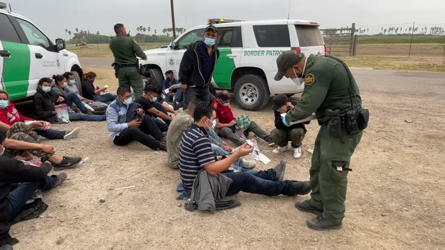transport officer searches immigrants before bussing them to a processing center after they crossed the border from mexico on april 13, 2021 in la... - crossing stock videos & royalty-free footage