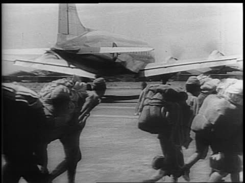 transport plane lands / japanese soldiers with backpacks leave their base / armed us troops exit planes, a soldier holds a monkey / a soldier raises... - wind点の映像素材/bロール