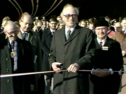 transport secretary nicholas ridley cuts a ribbon to officially open the epping forest section of the m25 motorway. 25 january 1984. - m25 video stock e b–roll