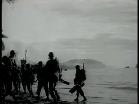 vídeos de stock e filmes b-roll de transport ship docked at water's edge w/ us soldiers walking down twin gang planks. us soldiers walking on beach. landing ship's bow hitting shore.... - pacific war