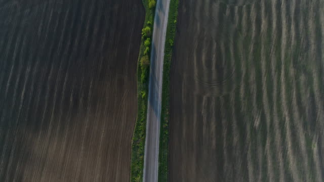 4K Transportation Aerial flight over long asphalt road between farmland