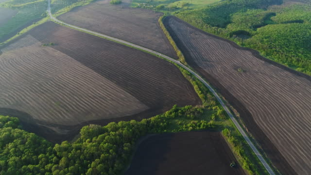 4K Transportation Aerial view of farmland green fields and road with cars