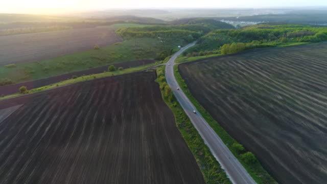4K Transportation Aerial view over asphalt road between farmland
