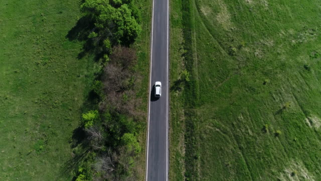 4k transportation aerial view white car driving on countryside road - scena rurale video stock e b–roll