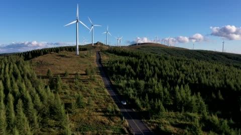 vídeos y material grabado en eventos de stock de 4k transportation aerial view white car driving on winding road towards wind generator - vehículo terrestre