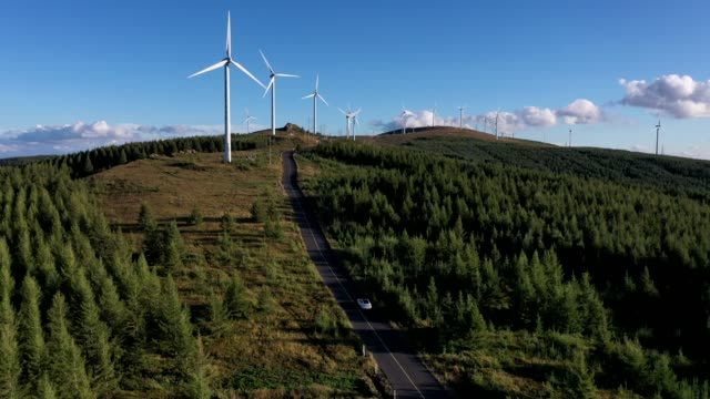 vidéos et rushes de 4k transportation aerial view white car driving on winding road towards wind generator - développement durable