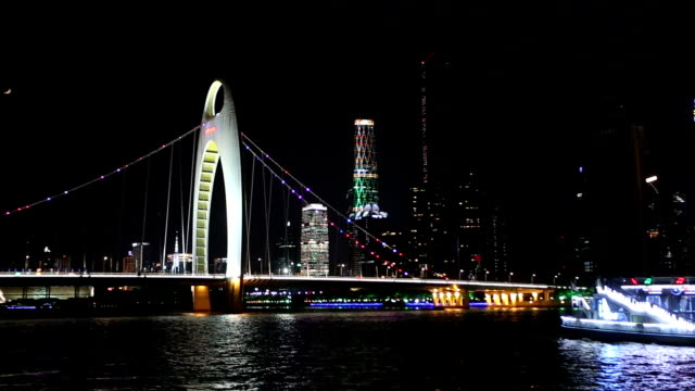 Transportation and skyline at bridge over river in Guangzhou at night,real time.