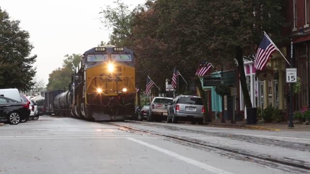 CSX Transportation freight trains roll through La Grange Kentucky US A CSX feight train rolls down a narrow suburban street in La Grange Kentucky