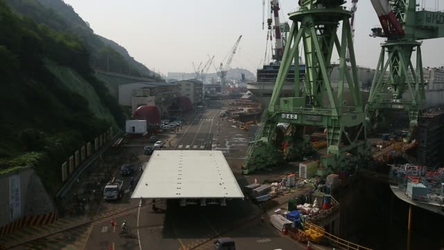 a transporter moves a part of a ship past vessels under construction in the dry dock at the hyundai mipo dockyard co shipyard an affiliate of hyundai... - 造船所の労働者点の映像素材/bロール