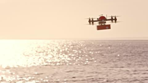 vidéos et rushes de slo mo uav transport de trousse de premiers soins au-dessus de la mer - drone