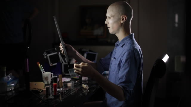Transsexual man applying make-up before the show