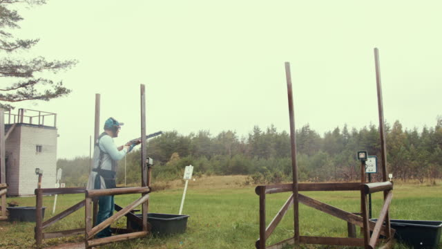 trap shooter in the autumn (slow motion) - tiro al piattello video stock e b–roll