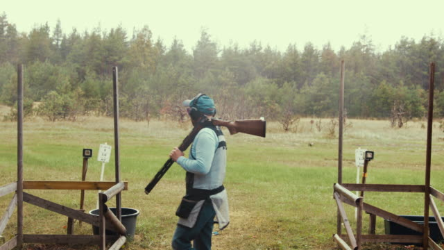 trap shooter walking during competition - tiro al piattello video stock e b–roll