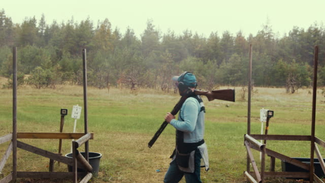 trap shooter walking during competition (slow motion) - tiro al piattello video stock e b–roll