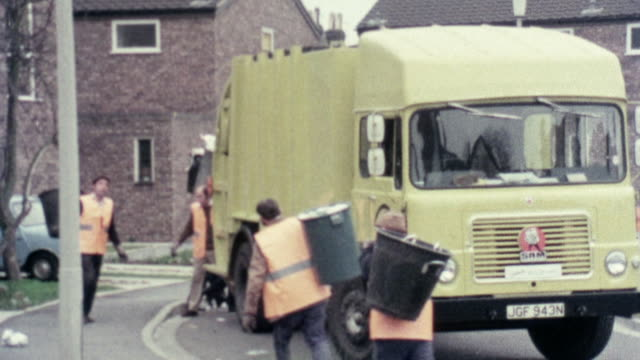 1976 montage trash collectors in a residential neighborhood dumping garbage into rear loading truck /  stevenage, hertfordshire, united kingdom - garbage truck stock videos and b-roll footage
