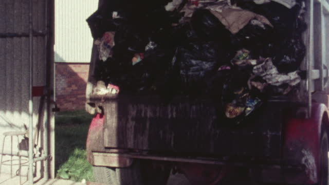 1976 montage trash falling out of a garbage truck and sitting in piles at a plant / hertfordshire, england, united kingdom - garbage truck stock videos and b-roll footage