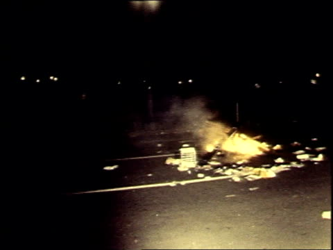 trash fire on the street / policeman watching trash fire on the street - 1969年点の映像素材/bロール