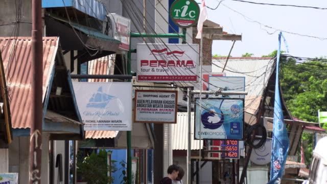 ws travel agency advertisements on street in city, labuan bajo, flores island, east nusa tenggara province, indonesia - フロレス点の映像素材/bロール