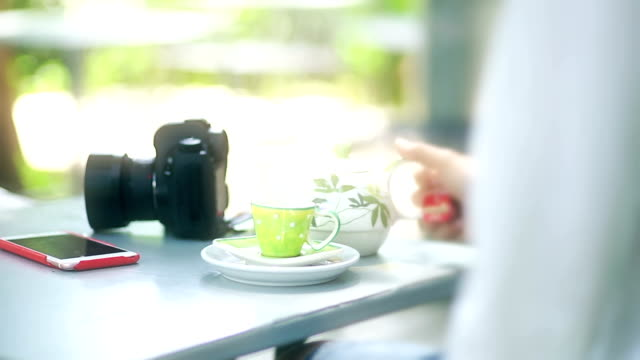 Travel and relaxing time concept with coffee cup, mirrorless camera and smartphone on the table in the cafe.