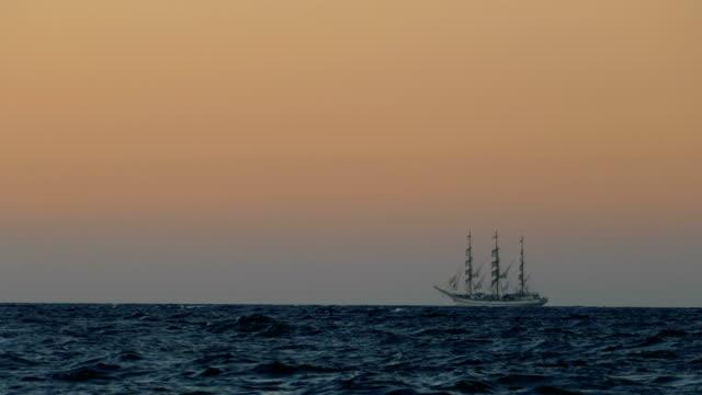 travel background - vintage sailing ship in full sail at sea at sunset