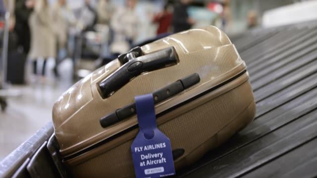 vídeos de stock, filmes e b-roll de mala de viagem sobre o carrossel de bagagens no aeroporto - etiqueta mensagem