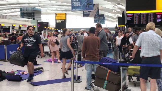 travel chaos at heathrow airport with passengers sleeping on the floor, due to weather conditions caused by heatwave - chaos stock-videos und b-roll-filmmaterial