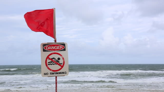 travel cinemagraph of a closed beach sign on dangerous beach, australia - flag blowing in the wind stock videos & royalty-free footage