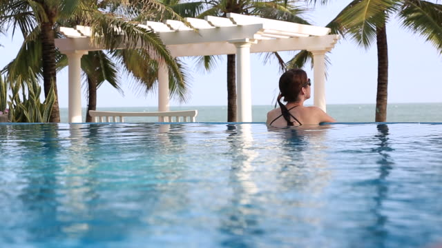 travel cinemagraph of woman relaxing inside infinity pool at tropical resort - tourist resort stock videos and b-roll footage