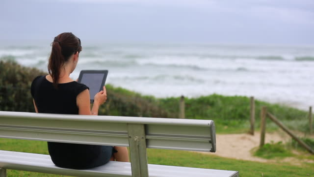 travel cinemagraph of woman using an electronic tablet on bench at beach - see other clips from this shoot 15 stock videos and b-roll footage