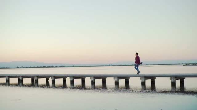 Travel Cinemagraph. Young man at a jetty in Ebro Delta