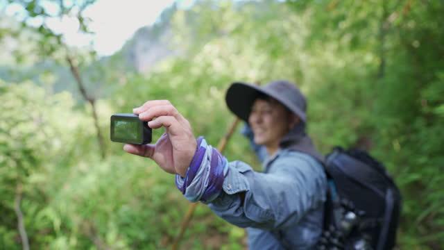 旅行ハイキングブロガーはビデオを記録します。山を歩く彼の手にアクションカメラを持っているハイカー - 外乗点の映像素材/bロール