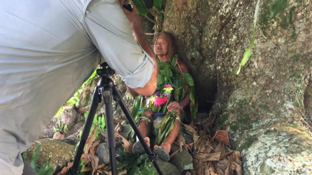 Travel photographer photographing an old aged Pacific Islander man praying under a tree in the rain forest