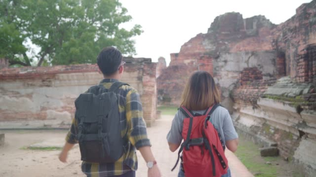 Traveler Asian couple spending holiday trip at Ayutthaya, Thailand, backpacker sweet couple enjoy their journey at amazing landmark in traditional city. Lifestyle couple travel holidays concept.