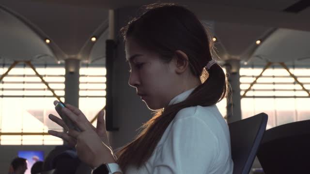 reisende asiatische frauen mit smartphone und checking fluginformationen am internationalen flughafen warten auf boarding - portable information device stock-videos und b-roll-filmmaterial