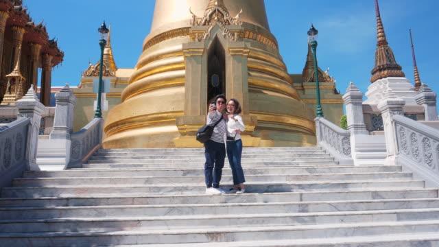 vidéos et rushes de traveler femmes asiatiques avec le voyage de couple de petite amie lesbienne dans la destination de voyage de bangkok et prenant le selfie - lieu de culte
