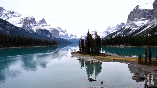 reisende kanufahren in kanadischen rockies reflexion auf maligne see auf spirit-insel in jasper nationalpark - quarz stock-videos und b-roll-filmmaterial