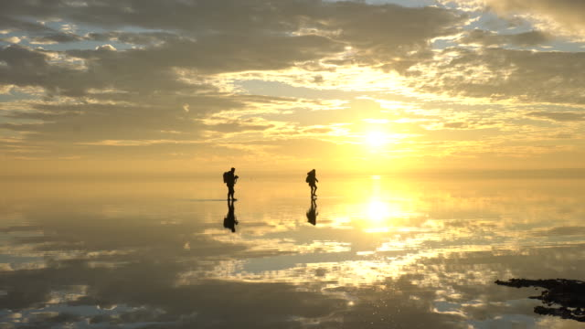 Traveler couple having fun walking on salt lake at sunset